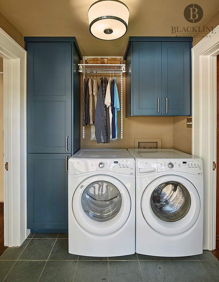 This laundry room remodel in Dallas's M-Streets features an LG Washer/Dryer and blue cabinets.